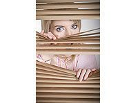 lady peering through blinds