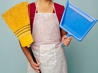 person in apron with broom and dustpan
