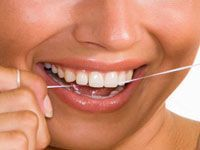 person smiling while flossing teeth