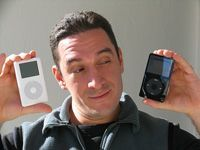 Guy between a white and black ipod