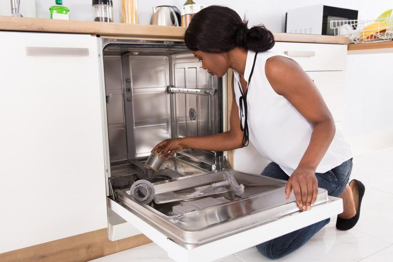 A woman cleaning her dishwasher.