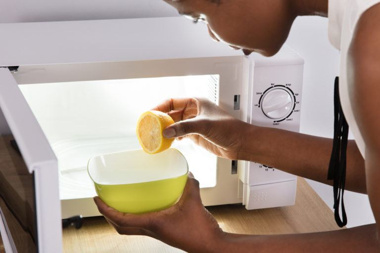A woman placing a water with fresh lemon squeezed into it into the microwave.