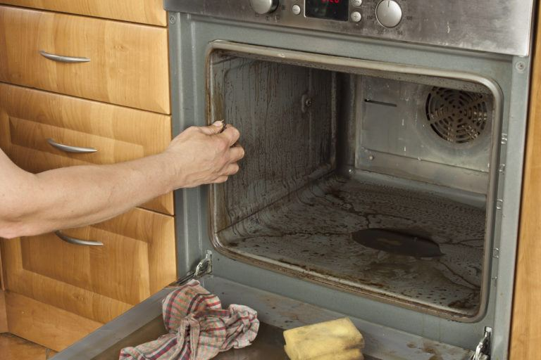 A person cleaning a very dirty oven.