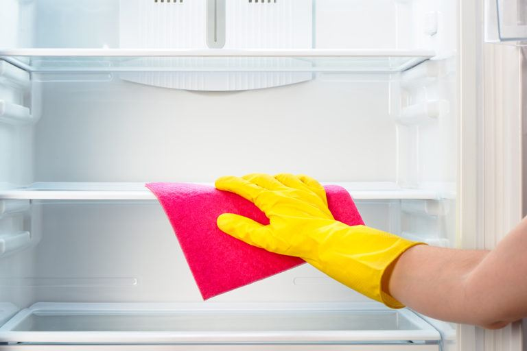 A person wiping down the inside of an empty refrigerator with a pink cloth.