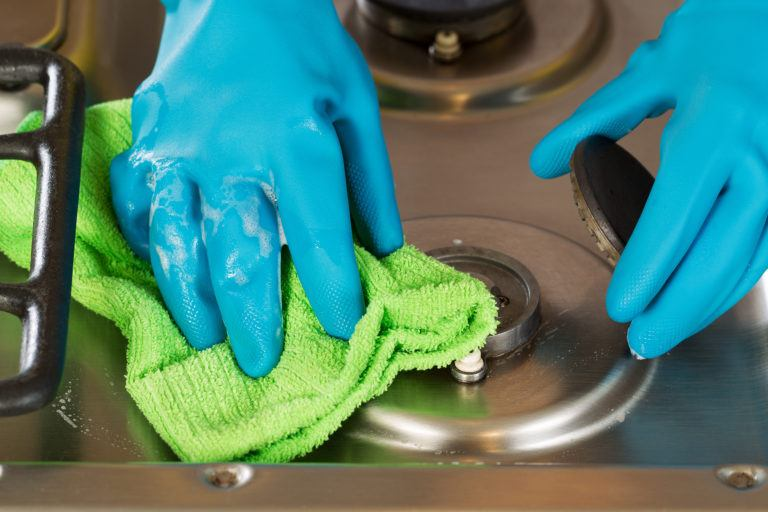 Gloved hands cleaning a stove top with a green microfiber cloth.