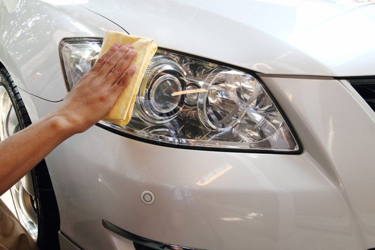 A hand wiping a white sedan headlight with a yellow microfiber cloth.