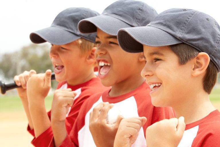 Three young boys with grey baseball hats on cheering at a baseball game.