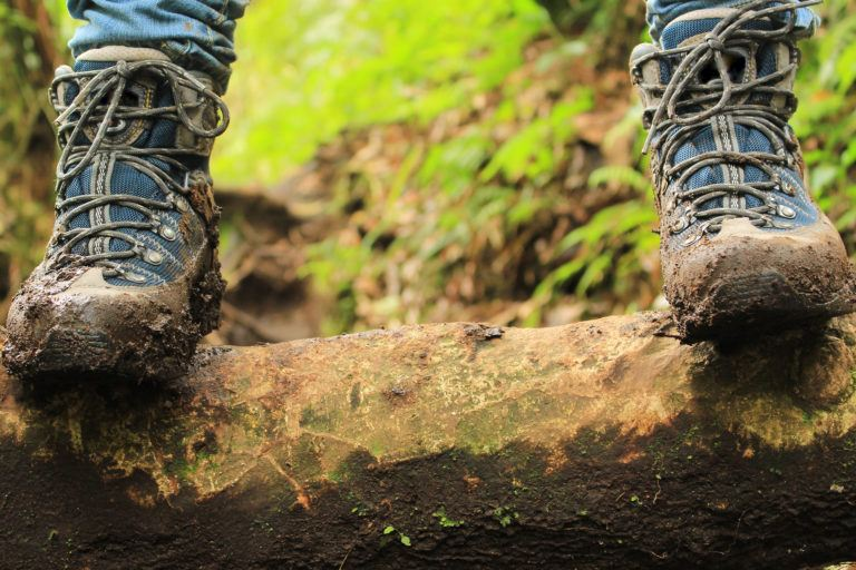 A person wearing muddy hiking boots standing on a log.