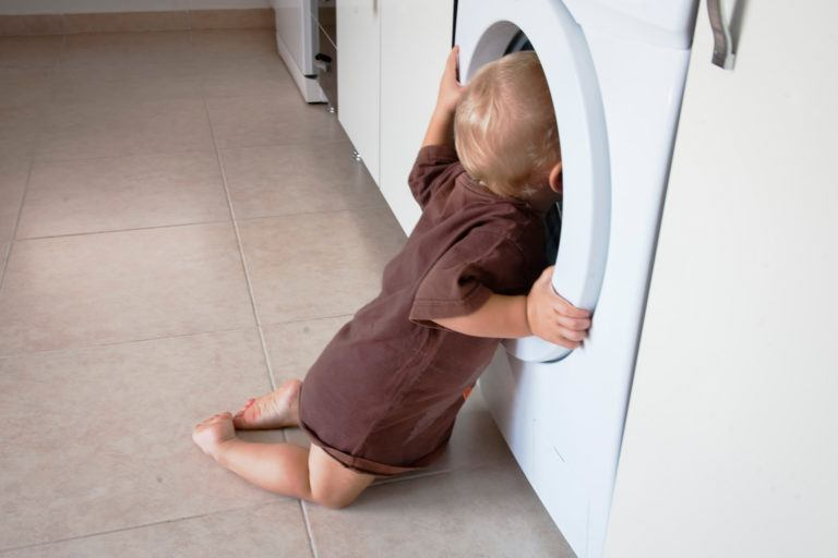 A baby inspecting a washing machine.