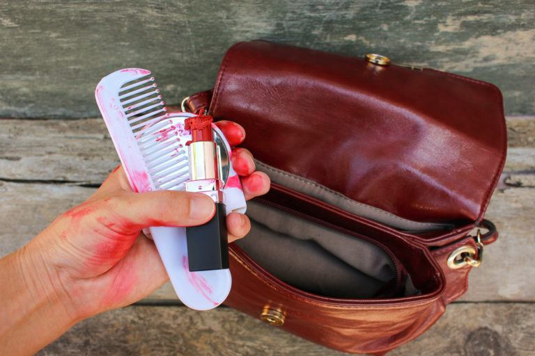 A hand pulls out melted lipstick and a messy comb and mirror from a purse.