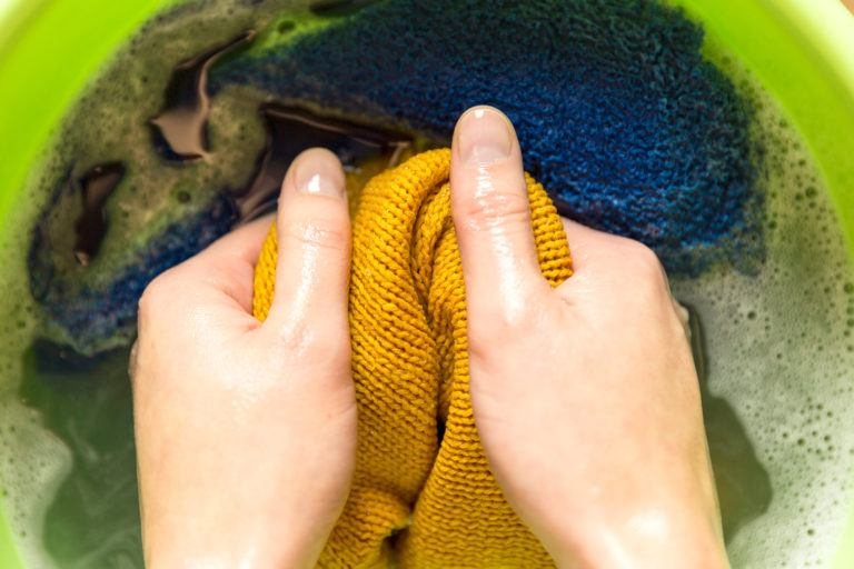 A person washing a wool sweater by hand.
