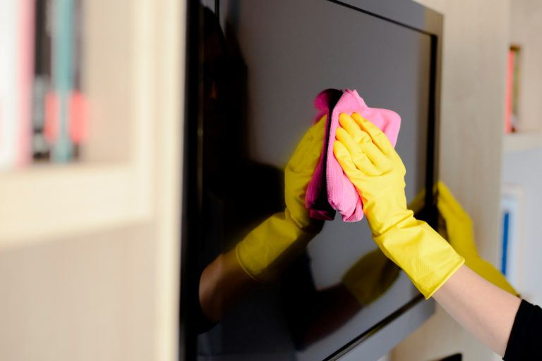 A person wearing gloves wiping down a flat screen tv.