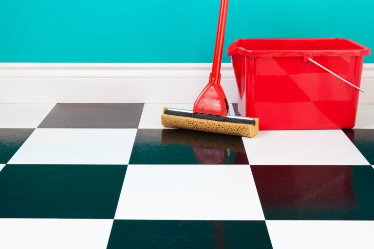 A mop and bucket sits on a black and white linoleum tiled floor.