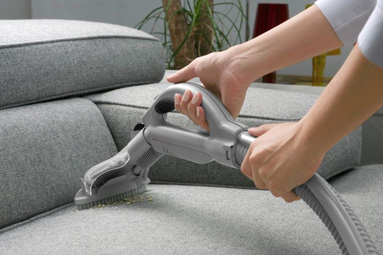 A person vacuuming a grey sofa.