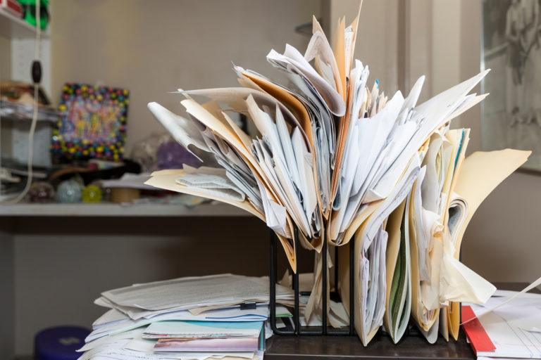 A desk overflowing with files.