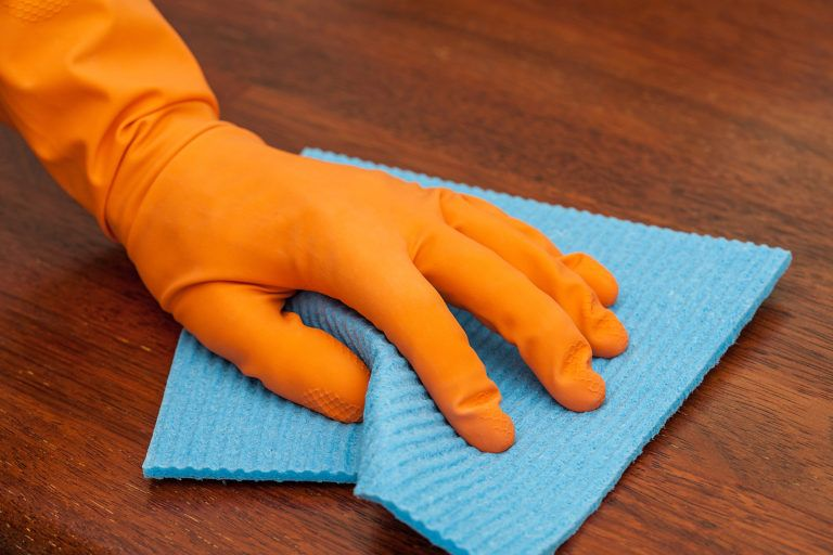 A gloved hand cleans a wooden piece of furniture with a blue rag.
