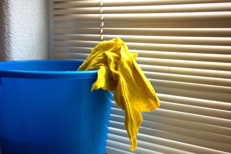 A blue bucket with a yellow rag sticking out sitting in front of closed blinds.
