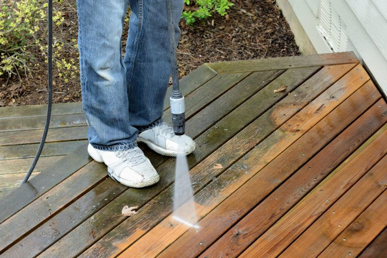 A person cleans a wooden deck with a pressure washer.