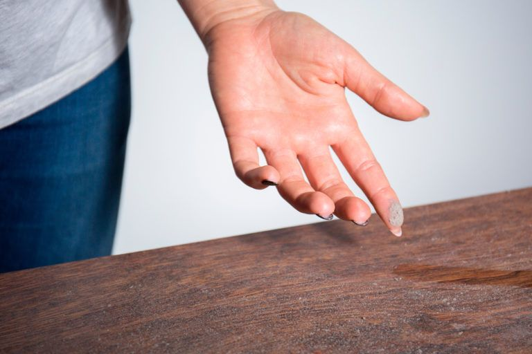 A person shows how dusty a wooden surface is by skimming their finger along its surface.