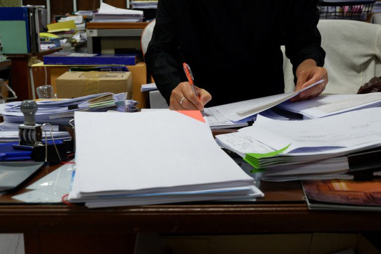 A person sits at a messy desk doing paperwork.