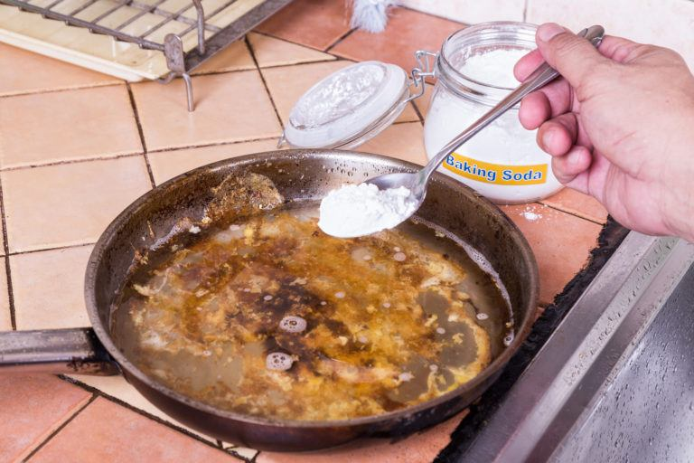 A person cleaning a dirty pan with water and baking soda.