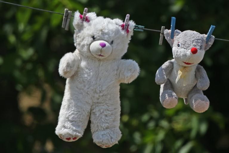 Two stuffed bears hanging on a clothes line to dry.