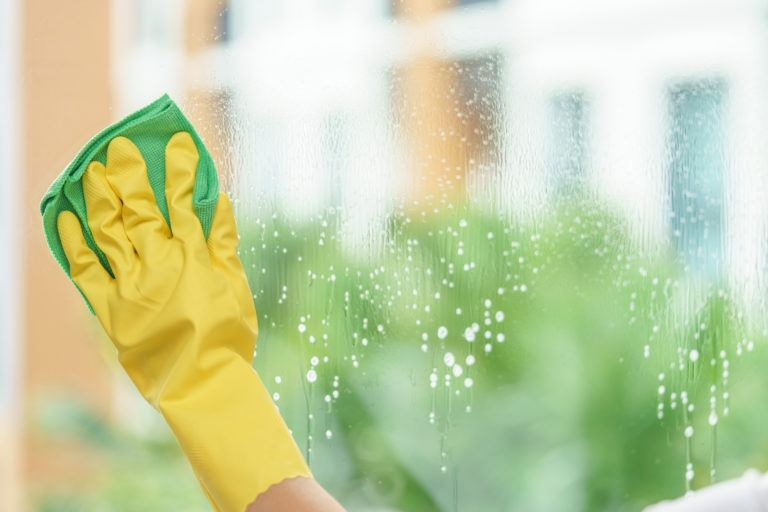 A gloved hand wipes down a wet window with a microfiber cloth.