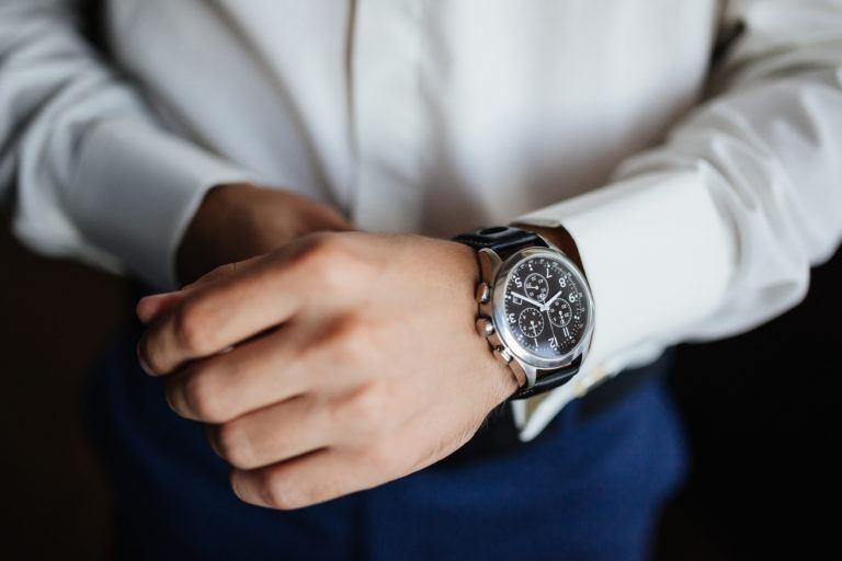 A man's wrist with a wristwatch.
