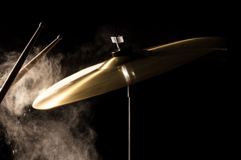 Cymbals being struck by drum sticks and dust flying off them.