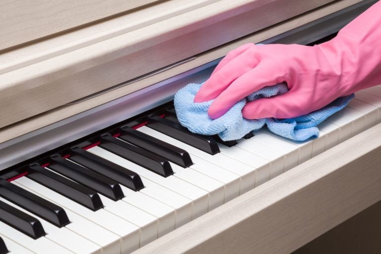 A gloved hand wiping down a piano with a microfiber cloth.