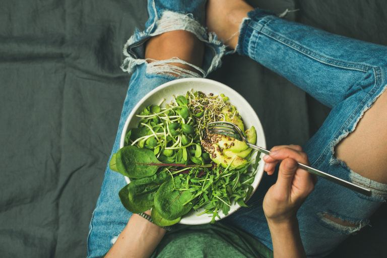 A person in jeans eating a large bowl of greens and avocado.
