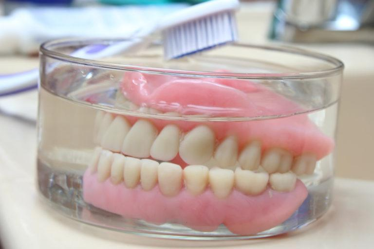 Dentures sitting in a glass jar with a toothbrush laying on the side of the jar.