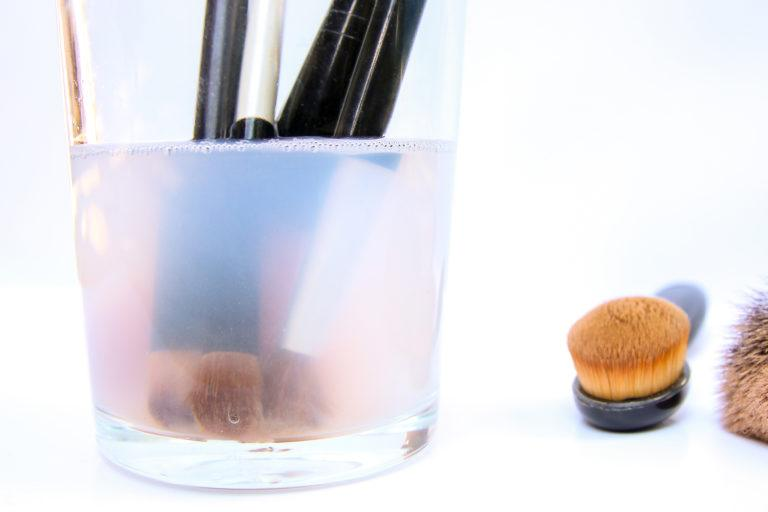 Makeup brushes soaking in a glass filled with water and vinegar.