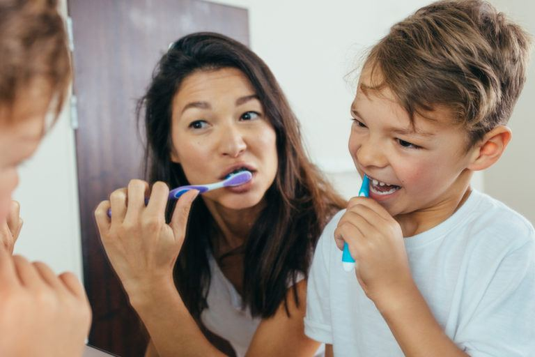 A mother and son brushing their teeth.