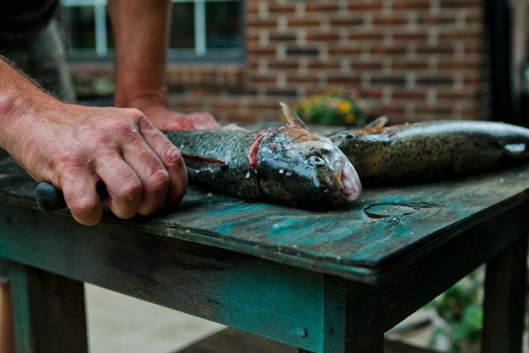 A man cleaning a trout outside.