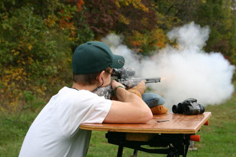 A young man shooting a muzzleloader rifle.