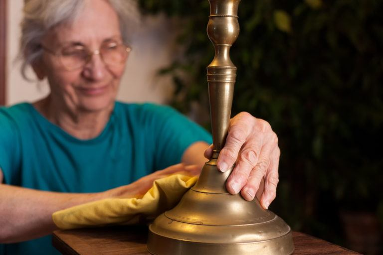 An elderly woman polishes a brass candlestick.