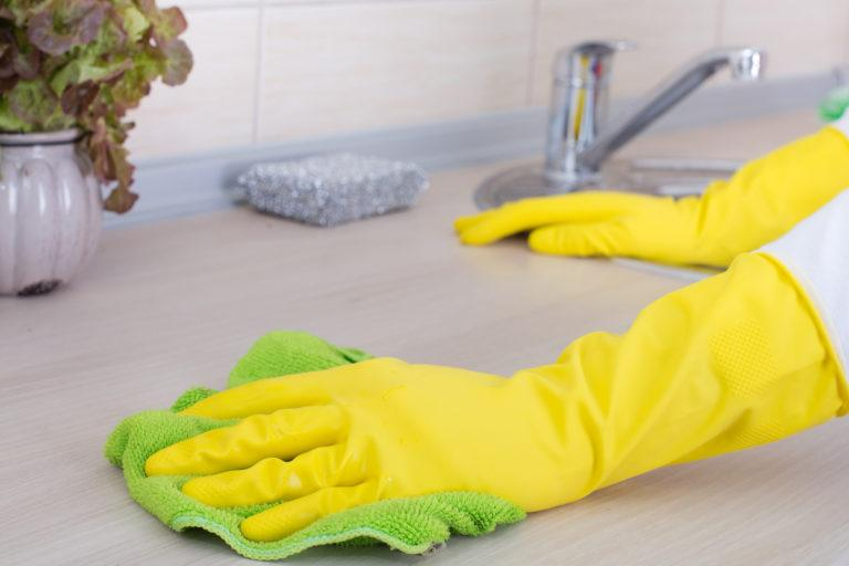 A gloved hand cleans a countertop with a cloth.