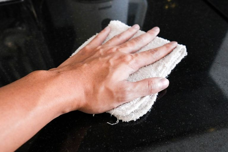 A Hand Wiping Down A Marble Countertop.