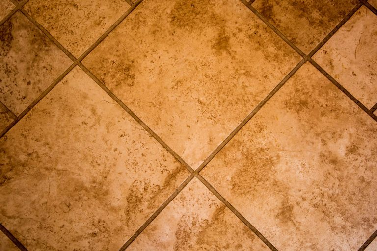 A floor tiled in travertine.
