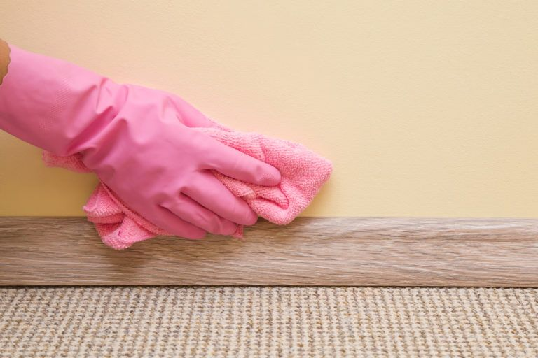 A gloved hand wiping down a wall.