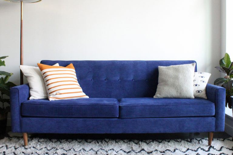 A blue suede couch in a living room.