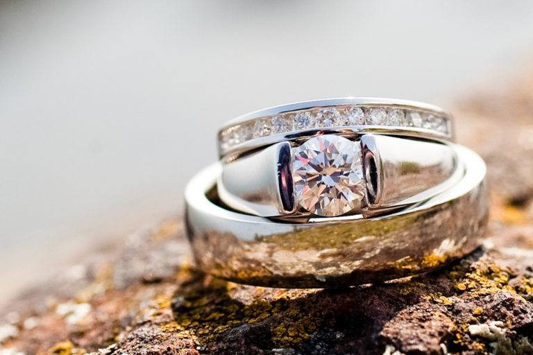 White gold wedding rings stacked on a rock.
