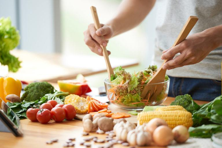 A person preparing a veggie salad.